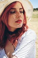 jeune femme rousse couvrant du soleil photo