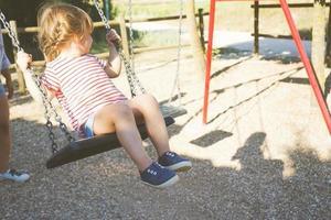 jeune fille dans une balançoire au parc photo