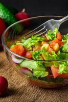 salade de légumes frais dans un bol en verre sur fond sombre plat d'été de saison végétalien bio photo