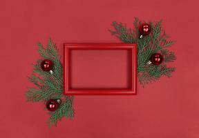 cadre rouge, branches d'arbres et boules décoratives. mise à plat monochrome de noël avec espace de copie. photo