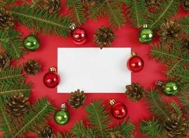 carte postale de vacances avec des branches de sapin, des cônes et des boules sur fond rouge. mise à plat de noël avec espace de copie. photo