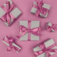 coffrets cadeaux emballés dans du papier kraft avec des rubans et des arcs roses doux. mise à plat monochrome festive. photo