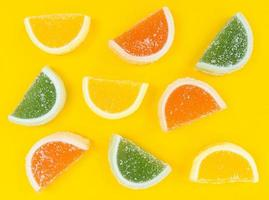tranches d'agrumes de marmelade multicolores en sucre sur fond jaune. photo