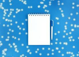 feuille de cahier vierge blanche et un stylo sur fond bleu avec des flocons de neige confettis épars. concept d'éducation de vacances. stock photo. photo