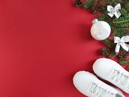 carte postale de vacances avec branches de sapin, cônes, arcs, babiole et baskets sur fond rouge. mise à plat de noël avec espace de copie. photo