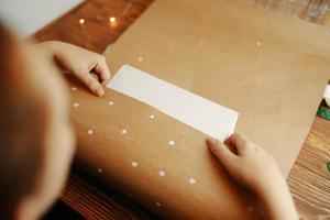 les mains de la fille enveloppent une boîte en carton dans du papier kraft sur une table en bois. photo