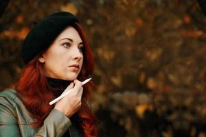 femme aux cheveux roux maussade dans le parc. photo