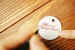 les mains des femmes avec un stylo écrivent l'inscription sur l'étiquette du cadeau. photo
