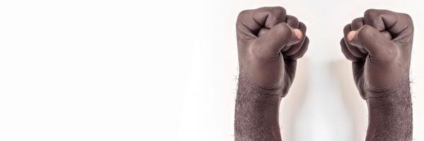 mains masculines serrées dans un poing sur un fond blanc. un symbole de la lutte pour les droits des noirs en Amérique. protester contre le racisme.banner. photo