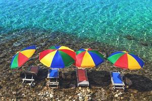 quatre parasols et transats dans l'eau sur la plage de galets photo