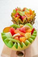 deux salades de fruits frais avec kiwi, banane, pêche, orange, orange rouge, abricot et melon dans un bol de melon et d'ananas fait à la main. photo