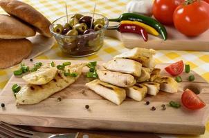 viande de poulet grillée sur plaque de bois avec légumes et olives en arrière-plan. photo
