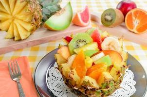 salade de fruits frais avec kiwi, banane, pêche, orange, orange rouge, abricot et melon dans un bol d'ananas fait à la main. photo
