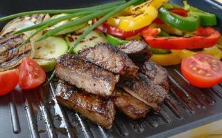 viande de boeuf grillée sur grill avec légumes grillés en arrière-plan. photo