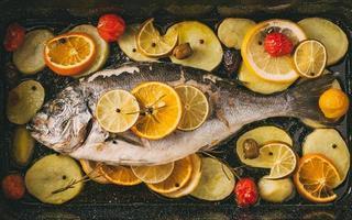 poisson daurade dans la plaque de cuisson au four avec pommes de terre, romarin, citron, orange, olives, tomates, oignon et citron vert. orata frais, préparation de poisson dorade. photo
