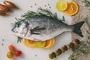 dorade de mer poisson sur table de cuisine avec romarin, citron, orange, olives, tomates, oignon et citron vert. orata frais, préparation de poisson dorade. photo