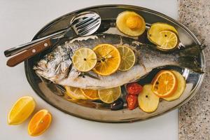 poisson daurade sur l'assiette au four avec pommes de terre, romarin, citron, orange, olives, tomates et citron vert. orata frais, préparation de poisson dorade. photo