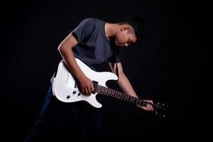 Jeune homme en blouson de cuir noir avec guitare électrique en studio photo