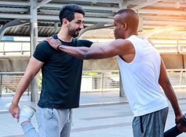 Deux beaux hommes portant des vêtements de sport réchauffent leur corps avant de faire de l'exercice à l'extérieur en ville photo