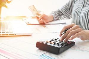 femme d'affaires utilisant une calculatrice et écrivant des notes. impôts, épargne, finances et concept d'économie photo