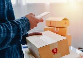 vue rapprochée de la boutique en ligne de l'homme, vendeur propriétaire de petite entreprise, entrepreneur emballage colis post-expédition boîte préparant le colis de livraison sur la table, concept entrepreneurial d'entreprise indépendante photo