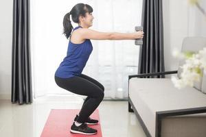 belle jeune femme sportive faisant des squats à la maison photo