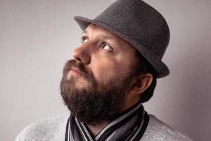 Jeune homme barbu hipster portant un chapeau et une écharpe gris photo