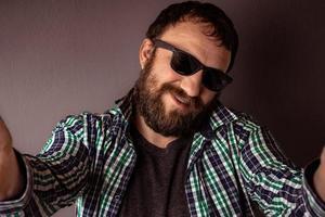 bel homme barbu hipster avec chapeau, lunettes de soleil et chemise prenant un selfie photo