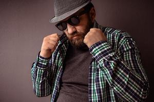 bel homme barbu hipster avec chapeau, lunettes de soleil et chemise photo