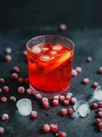 aperol spritz avec de la glace et des canneberges sur fond noir. photo