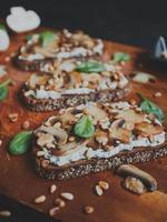 savoureuse bruschetta fraîche aux champignons, épinards, ail, fromage à la crème et pignons, sur une planche de bois, sur fond sombre. photo