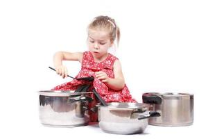 petit enfant utilisant des accessoires de cuisine s'amusant photo