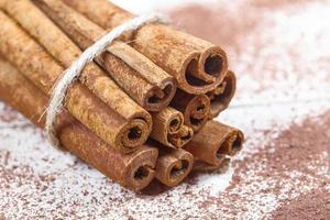 bâtons de cannelle et accessoires en poudre de cacao pour une soirée d'hiver confortable près de la cheminée avec un verre de vin photo