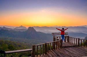 les jeunes ressentent l'air frais du matin avec une mer de brume devant mae hong son baan jabo thaïlande photo