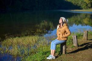 femme relaxante visage yeux fermés assis au bord de la rivière. photo
