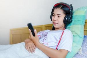 femme endormie en écoutant des écouteurs. fille asiatique dormant sur le canapé en écoutant des écouteurs. photo