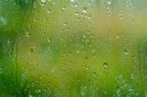 gouttes d'eau de texture sur le verre vert photo