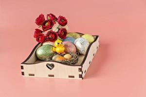 oeufs de pâques dans un nid naturel sur un plateau en bois, des fleurs et un poulet décoratif sur fond rose photo