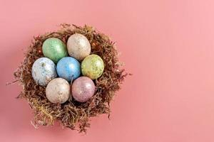 oeufs de pâques dans un nid naturel avec de la mousse sur fond rose. vue d'en-haut photo