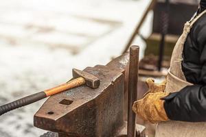 le garçon, le fils du forgeron, se tient à l'enclume. le processus de forge photo