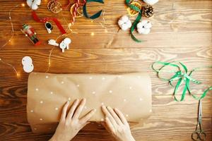 vue de dessus des mains des femmes emballant un cadeau de Noël sur une table en bois. photo