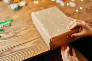 gros plan des mains des femmes emballant le cadeau de Noël. photo