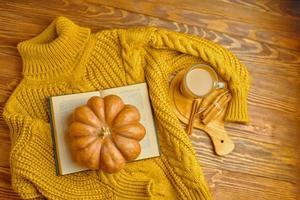 pull confortable tricoté, livre ouvert et citrouille sur fond en bois. photo