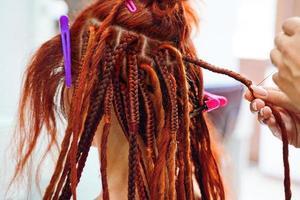 les mains du coiffeur tressent les dreadlocks au gingembre de la fille. photo
