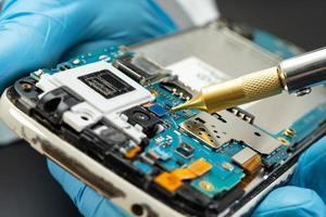 technicien réparant l'intérieur du disque dur en fer à souder. circuit intégré. le concept de données, de matériel, de technicien et de technologie. photo