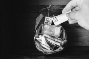 la main tient une note de papier de cinquante euros ajoute au bol d'épargne. avoirs d'investissement en monnaie énorme. photo