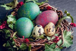 oeufs de pâques avec décoration.oeufs de caille et de poule dans un nid d'oiseaux. photo