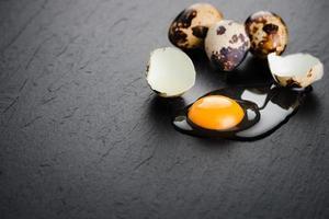 oeufs de caille sur fond de pierre noire, oeuf de caille cassé et fêlé, jaune d'oeuf de caille. produit biologique. photo