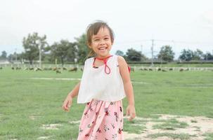 fille heureuse d'enfant s'amusant dans la ferme de moutons. photo