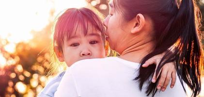 mère réconfortant sa petite fille qui pleure dans le parc. notion de parentalité. photo